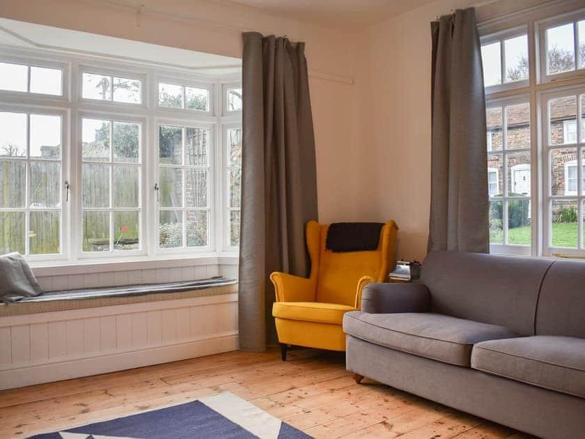 Living room with wooden floor overlooking the garden | Hiham Lodge, Winchelsea, near Rye