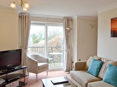 Living room with patio doors leading to garden | Bilsdale - Sutton Hall Cottages, Sutton-under-Whitestonecliffe near Thirsk