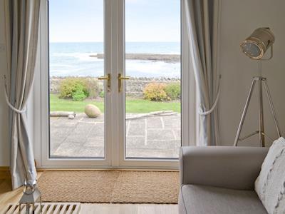 French doors in living room overlooking the garden and shoreline | Waters Edge, Craster, near Alnwick