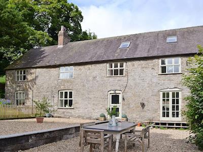 Rear of property with seating area | Upper Woodhouse Farm, Rhos-Y-Meirch, near Knighton