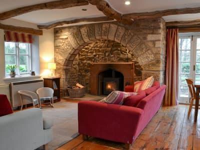 Living room with stone fireplace & log burner | John Peel House, Ruthwaite, near Bassenthwaite