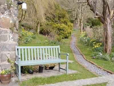 Tranquil seating area within garden | The Cottage - Dolgenau, Llawr-y-Glyn, Caersws