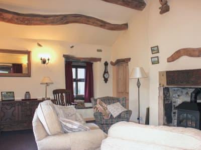 Beamed living room with wood burner | Benchmark Cottage, Haworth