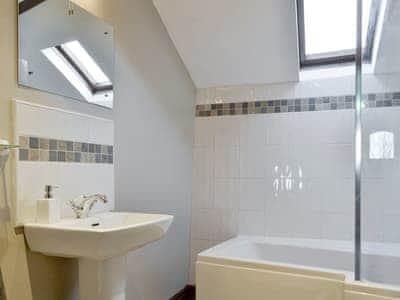 En-suite bathroom with shower over bath | The Hayloft - Saddleback Cottages, Broughton Beck, near Ulverston