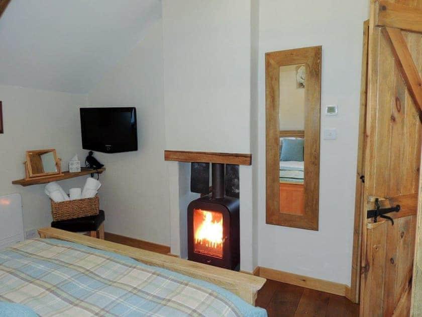 Impressive double bedroom with dual aspect wood burner | The Coach House Loft - Dolgoy Cottages, Llangrannog
