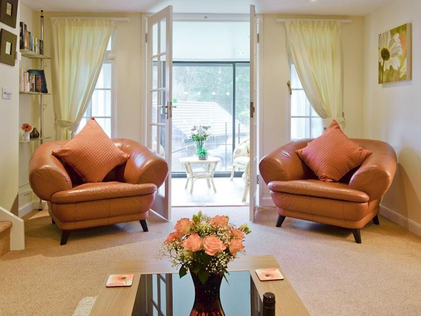 Stylish lounge with French doors to conservatory | Riverside Cottage - Rosecraddoc Manor, Liskeard
