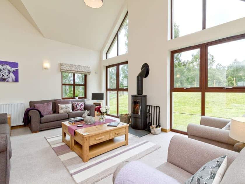 Beautiful living room with floor to ceiling windows and woodburner | Birch Corner, Aviemore