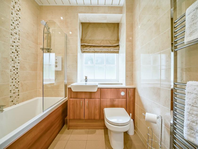 Modern bathroom with shower over the bath | MacKenzie Cottage - Blairquhan Castle Estate, Straiton, near Maybole
