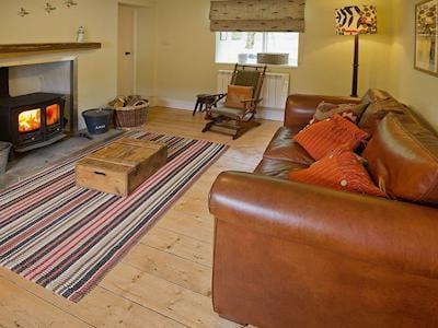 Cosy wood-floored living room with log burning fire and large leather sofa | Laggan Bridge Cottage, Laggan Bridge near Invergarry